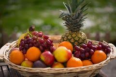 Obstkorb mit Mischfrüchten, mit grünem Hintergrund Stockfotos