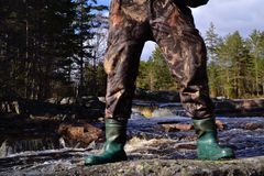 Obstructed view. Waterfall with Obstructed view from mans two Legs with boots Stock Photography