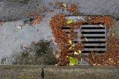 Obstruiu um dreno da rua durante uma tempestade da chuva fotos de stock