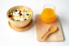Obstsalat mit Jogurt auf einer hölzernen Schüssel und einem Orangensaft lizenzfreies stockbild