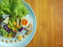 Obstsalat und Salatsoße mit hölzernem Hintergrund stockfotografie