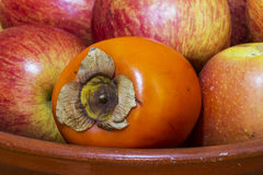 Kakifarbig zwischen Äpfeln. Stockfoto