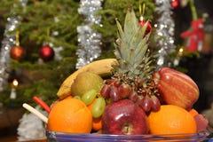 Obstschale mit Weihnachtsbaum im Hintergrund Lizenzfreies Stockfoto