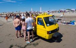 Obstverkäufer mit gelbem Fahrzeug auf drei Rädern auf dem Strand Stockbilder