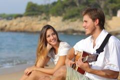Obsługuje flirtować bawić się gitarę podczas gdy dziewczyna patrzeje on zadziwiał Zdjęcie Royalty Free
