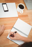 Obsługuje writing na ślimakowatym notatniku przy biurkiem w biurze Obrazy Stock