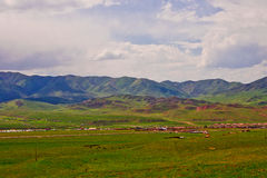 Obszar trawiasty, wioska i góra, Obraz Royalty Free