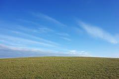 Obszar trawiasty z białymi chmurami zdjęcie royalty free