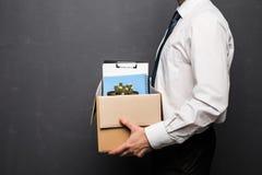 Obtenção despedido Imagem colhida do homem de negócios considerável no vestuário formal que guarda uma caixa com seu material, no imagem de stock