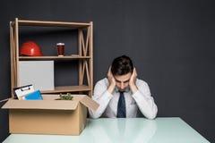 Obtenção despedido O homem de negócios considerável no terno está sentando-se tristemente na tabela no escritório perto da caixa  fotografia de stock royalty free