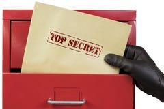 Obtenant les documents extrêmement secrets d'un classeur rouge, au-dessus d'un fond blanc Photographie stock libre de droits