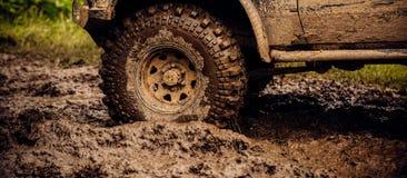 Obtendo fora o trajeto batido Rodas de carro no terreno do estepe que espirra com a sujeira SUV ou offroader na estrada da lama I foto de stock royalty free