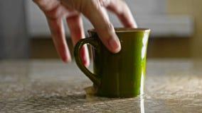 Obtenez la tasse verte outre de la table banque de vidéos