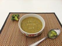 Obtenez meilleur bientôt écrit en potage aux légumes avec la cuillère photo libre de droits