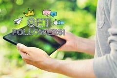 Obtenha a seguidores o conceito com o homem novo que guarda seu tablet pc fotos de stock royalty free