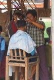 Obtention d'une coupe de cheveux au marché hebdomadaire Images stock