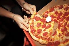 Obtention d'une tranche de pizza de pepperoni fraîche Photographie stock libre de droits