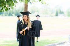 Obtention du diplôme : Étudiant Standing With Diploma avec des amis derrière Photographie stock libre de droits