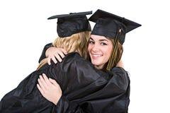 Obtention du diplôme : Les amies donnent une étreinte après obtention du diplôme Image stock