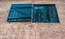 Obturador de madeira preto da janela em uma construção de tijolo velha Fotografia de Stock
