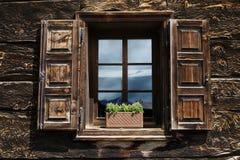 Obturador de madera abierto hermoso de la ventana con las flores que reflejan el cielo azul imagenes de archivo