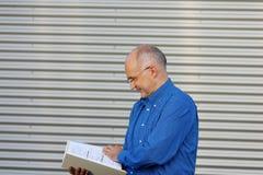 Obturador de Reading Book Against del hombre de negocios Foto de archivo libre de regalías