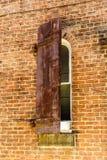 Obturador semi-fechado muito velho com a janela velha da oxidação em uma construção de tijolo Fotos de Stock Royalty Free