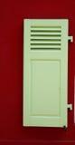 Obturador verde de la ventana de una casa roja fotografía de archivo libre de regalías