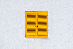 Obturadores amarelos da janela e parede branca Imagens de Stock