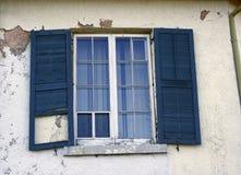 Obturadores azuis na construção velha do estuque da janela de vidro Foto de Stock