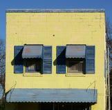 Obturadores azules en el edificio amarillo Imágenes de archivo libres de regalías