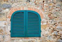 Obturadores azules en una pared de piedra toscana antigua foto de archivo