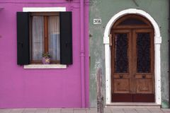 Obturadores brilhantemente coloridos da janela da parede do rosa e do verde e entrada Burano Veneza do arco Fotografia de Stock