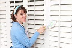 Obturadores de la ventana de la polvoreda de la mujer Foto de archivo