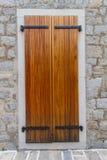 Obturadores de madera grandes en una pared de piedra Imagenes de archivo