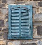 Obturadores exteriores del vintage en la estructura envejecida de la pared de piedra Fotos de archivo libres de regalías