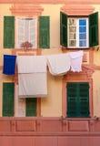 Obturadores, ventanas falsas y ropa colgando en un fa mediterráneo Foto de archivo libre de regalías