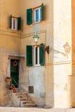 Obturadores y puerta en fachada mediterránea antigua con una lámpara po Fotografía de archivo