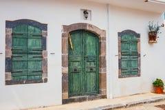 Obturadores y puertas verdes en una pared blanca Fotografía de archivo