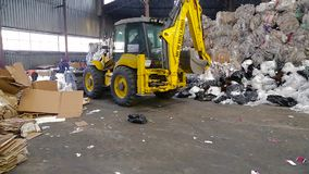 Large warehouse of waste paper in a factory. Obuhov, Ukraine - Fedruary 2017: Warehouse with recyclable materials at the garbage processing factory. Loader stock video footage
