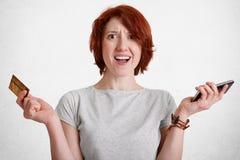 Oburzona imbirowa kobieta intrygował wyrażenie, chwyty w jeden ręka mądrze telefonie w innej kredytowej karcie, nieszczęśliwego w zdjęcie royalty free