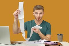 Oburzony mężczyzna trzyma czeki, no rozumieć od dokąd duże sumy, gotowe nieprzewidziani koszty obraz royalty free