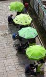Obuwiani shiners pod zielonymi parasolami zdjęcia stock
