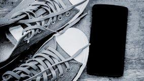 Obuwiany i czarny smartphone na drewnianej podłoga Obrazy Royalty Free