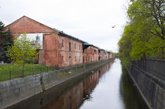 Obvodny Canal protected old unplastered buildings from a red brick Admiralty warehouses in Kronddshtat Russia Royalty Free Stock Photography