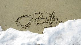 OBX written in the sand. Being washed out by a wave royalty free stock photos