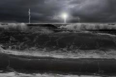 Océan dramatique, ciel nuageux foncé avec le phare de foudre dedans pour Images stock