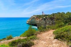 Océan et phare bleus sur la falaise Photographie stock libre de droits