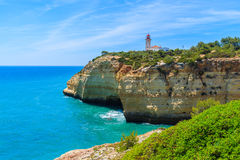 Océan et phare bleus sur la falaise Photographie stock