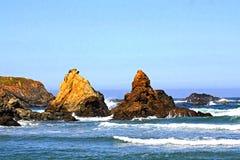 Océano azul tranquilo cerca de una playa rocosa Foto de archivo libre de regalías